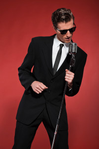 Retro fifties singer with vintage microphone and sunglasses. Studio shot.